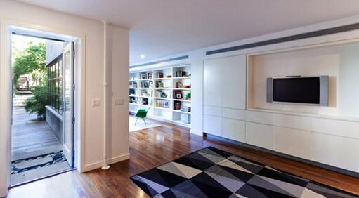 该电视背景墙使用白色面漆板材制作成收纳柜隐藏于墙